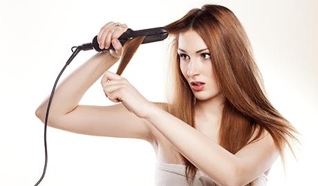 アイロンで髪を巻く女性