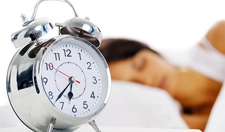 目覚まし時計と眠る女性